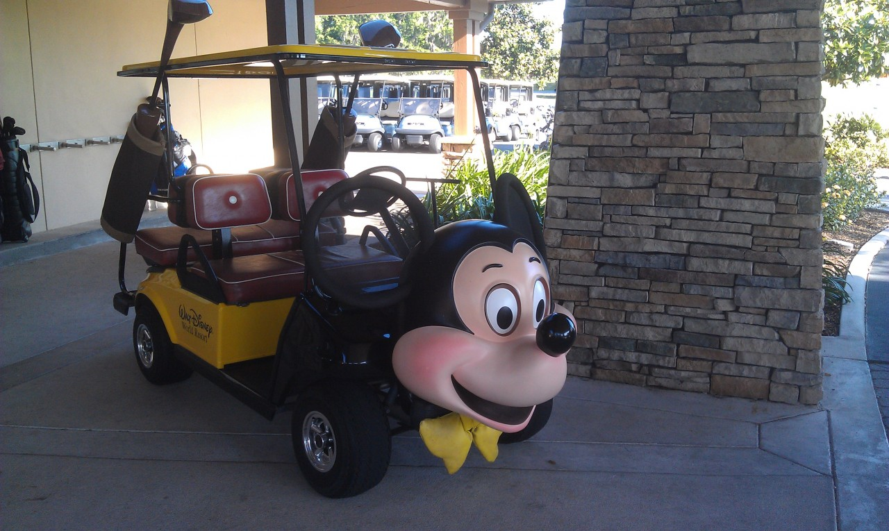 The Mickey Mouse golf cart parked near the clubhouse entrance.