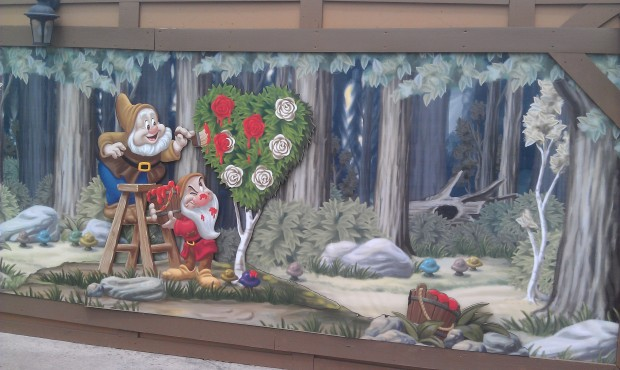 Dwarfs painting the roses red, on the construction wall across from Mad Tea Party