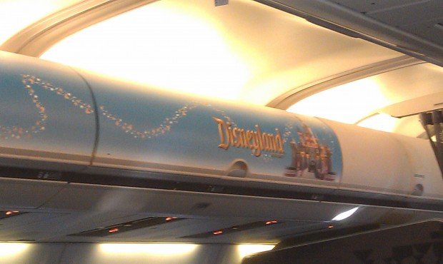 Onboard the plane a Disneyland sign on the overhead bin