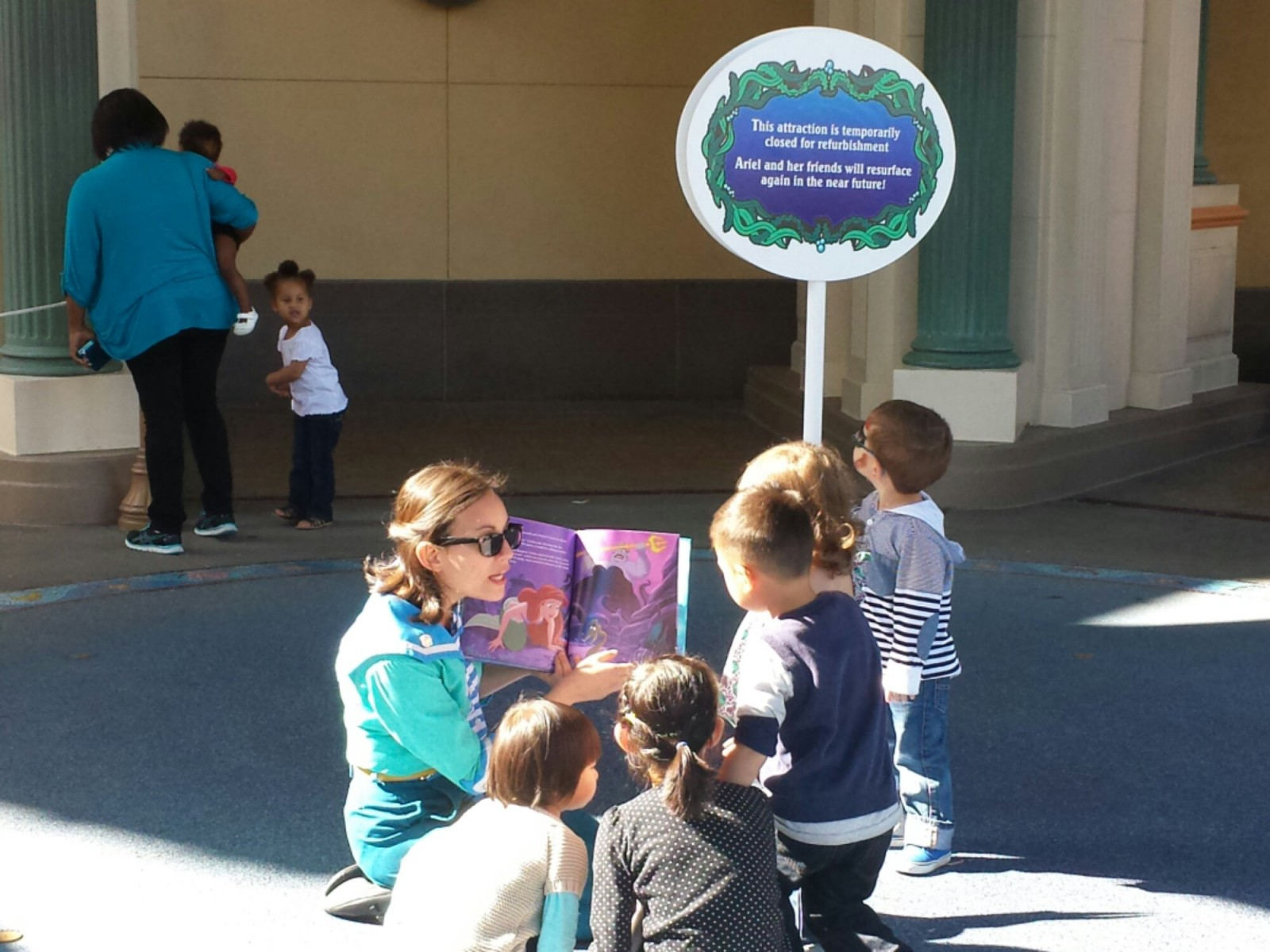 A cast member reading a Little Mermaid book to guests since the attraction is closed
