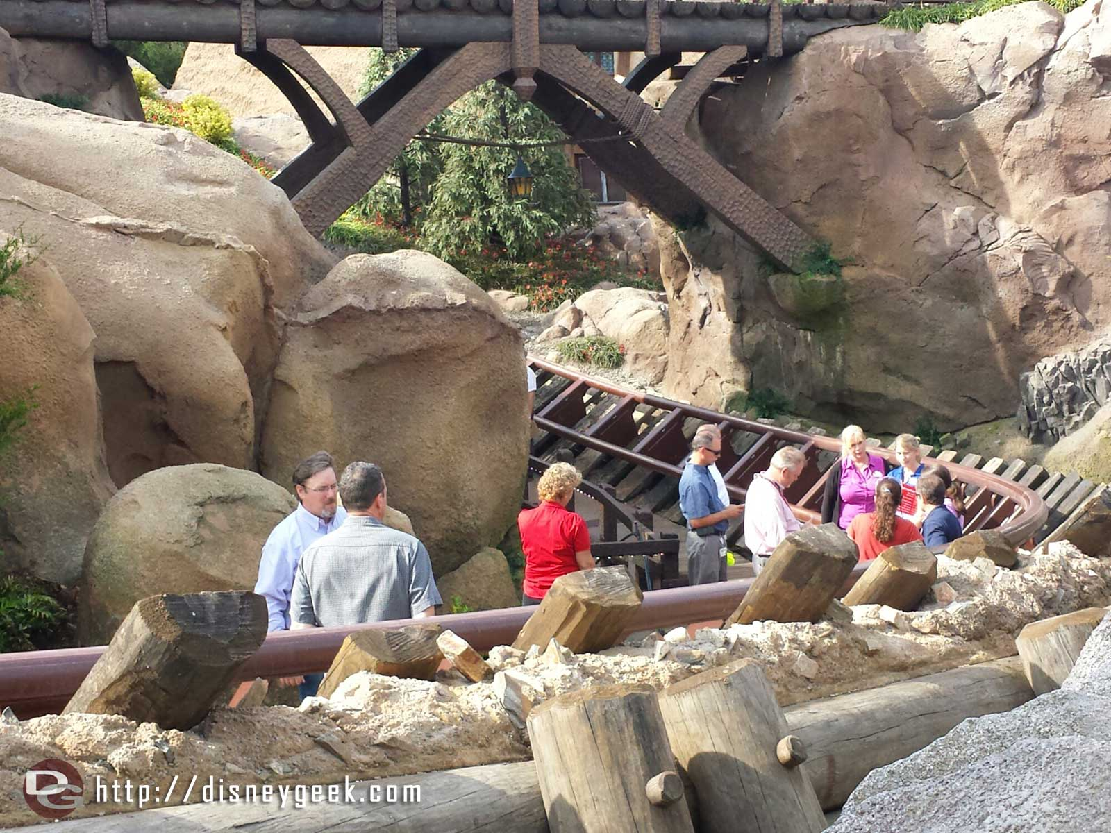 Some type of meeting going on along the Seven Dwarfs Mine Train track.  Looks to be a walkthrough/punch list check
