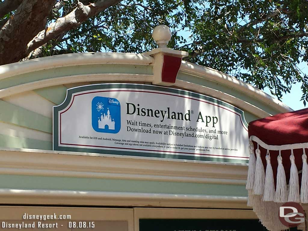 The #Disneyland line board advertises the new official app