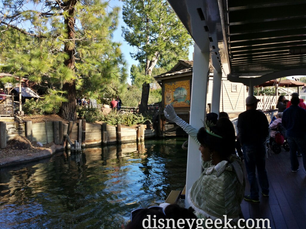 Princess Tiana waving to guests in Frontierland as the Mark Twain approaches port