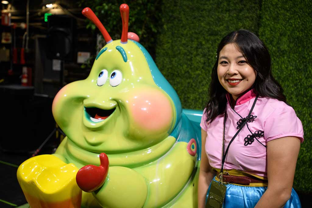 A guest poses with Heimlich's Chew Chew Train on display from the Walt Disney Archives at D23's 10-Year FAN-niversary Celebration at the Walt Disney Studios, March 10, 2019.