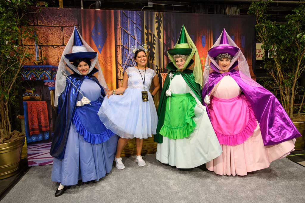 A guest poses with Sleeping Beauty's Flora, Fauna, and Merryweather at D23's 10-Year FAN-niversary Celebration at the Walt Disney Studios, March 10, 2019.