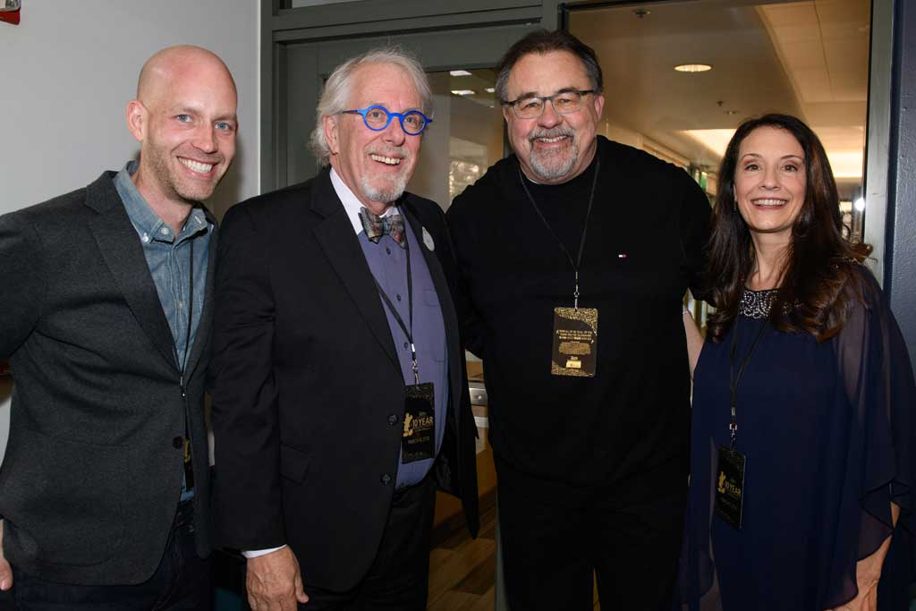 Left to right, Bret Iwan (voice of Mickey Mouse), Bill Rogers (voice actor, announcer at Disneyland), producer Don Hahn, and Camille Dixon (voice actor, announcer at Disney California Adventure) at D23's 10-Year FAN-niversary Celebration at the Walt Disney Studios, March 10, 2019.