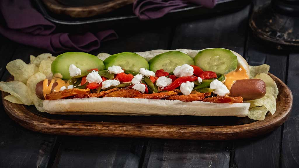At Refreshment Corner at Disneyland Park, guests will find this Hades-inspired foot-long all-beef hot dog served with harissa aioli, lemon pickled cucumbers, oven dried tomatoes, sautéed peppers and feta cheese. (David Nguyen/Disneyland Resort)