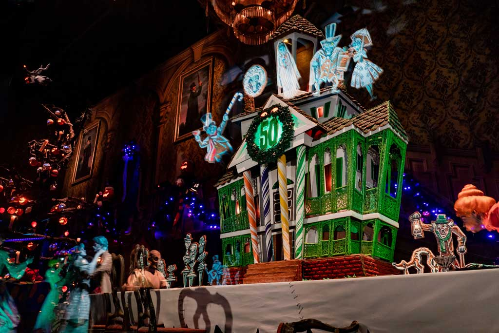 "The Haunted Mansion transforms into Haunted Mansion Holiday for Halloween Time and the holiday season, inspired by the Walt Disney Pictures classic ""Tim Burton's The Nightmare Before Christmas."" As part of the transformation, a gingerbread house sits on the dining table in the Grand Hall as the scent of tasty gingerbread fills the air. This year, the nearly 10-foot tall centerpiece celebrates the Haunted Mansion's 50th anniversary, complete with 15 spirited Haunted Mansion residents made of gingerbread cookies. (David Nguyen/Disneyland Resort)"