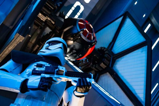 A First Order Stormtrooper stands guard in a Star Destroyer hangar bay beneath a docked TIE fighter in Star Wars: Rise of the Resistance, the groundbreaking new attraction opening Dec. 5, 2019, inside Star Wars: Galaxy's Edge at Disney's Hollywood Studios in Florida and Jan. 17, 2020, at Disneyland Park in California. Guests enter the hangar bay after their ship is caught in the Star Destroyer's tractor beam. (Matt Stroshane, photographer)