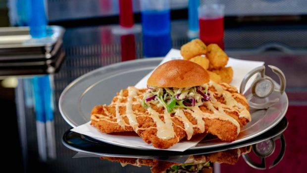Experiment No. EE90: Not So Little Chicken Sandwich features fried chicken breast with teriyaki and red chili sauces, pickled cabbage slaw and crispy potato tots. (David Nguyen/Disneyland Resort)