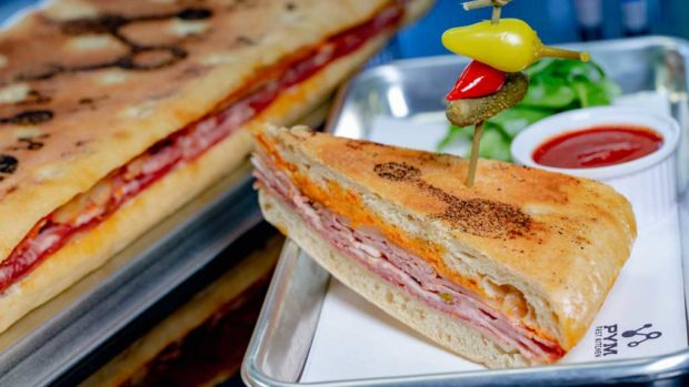 Experiment No. EE10: Pym-ini, a panini on toasted focaccia with salami, rosemary ham, provolone, sun-dried tomato mayonnaise and arugula with marinara dipping sauce, which can be served by the slice or as a long, multi-portion sandwich. (David Nguyen/Disneyland Resort)