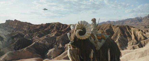 Tusken Raider rides on a bantha below with the Razor Crest in THE MANDALORIAN, season two. © 2020 Lucasfilm Ltd. & TM. All Rights Reserved.