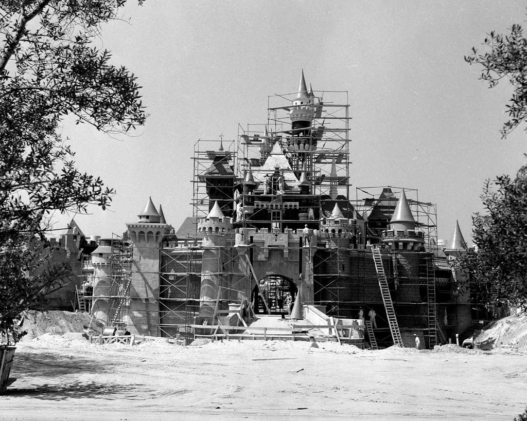 """SLEEPING BEAUTY CASTLE UNDER CONSTRUCTION (1955) – Two months before she """"awoke"""" to opening day visitors, this Disneyland landmark was getting a few final touches from construction workers. Walt Disney wanted this castle to be a friendly and welcoming presence in his park so it was built on a smaller scale than its European counterparts."""