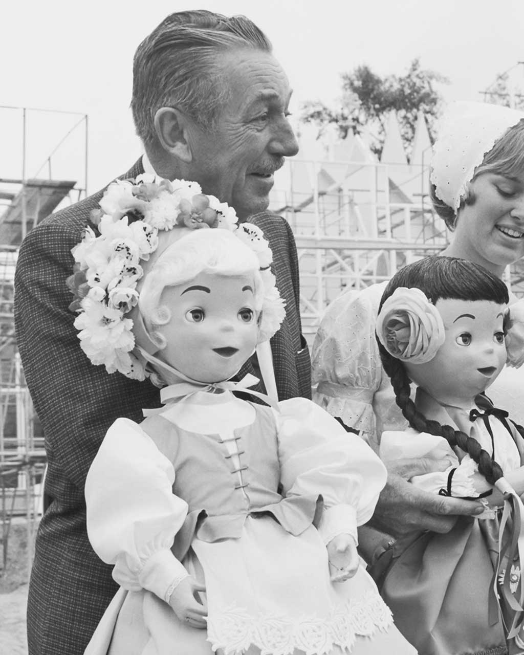"""WALT DISNEY -- Walt Disney """"meets"""" some residents of the 'it's a small world' attraction at Disneyland in California, during construction in May, 1966. One of the most popular Disney attractions of all time, the show is a fun-filled and whimsical salute to the children of the world that conveys its message of peace and harmony through the international language of music."""