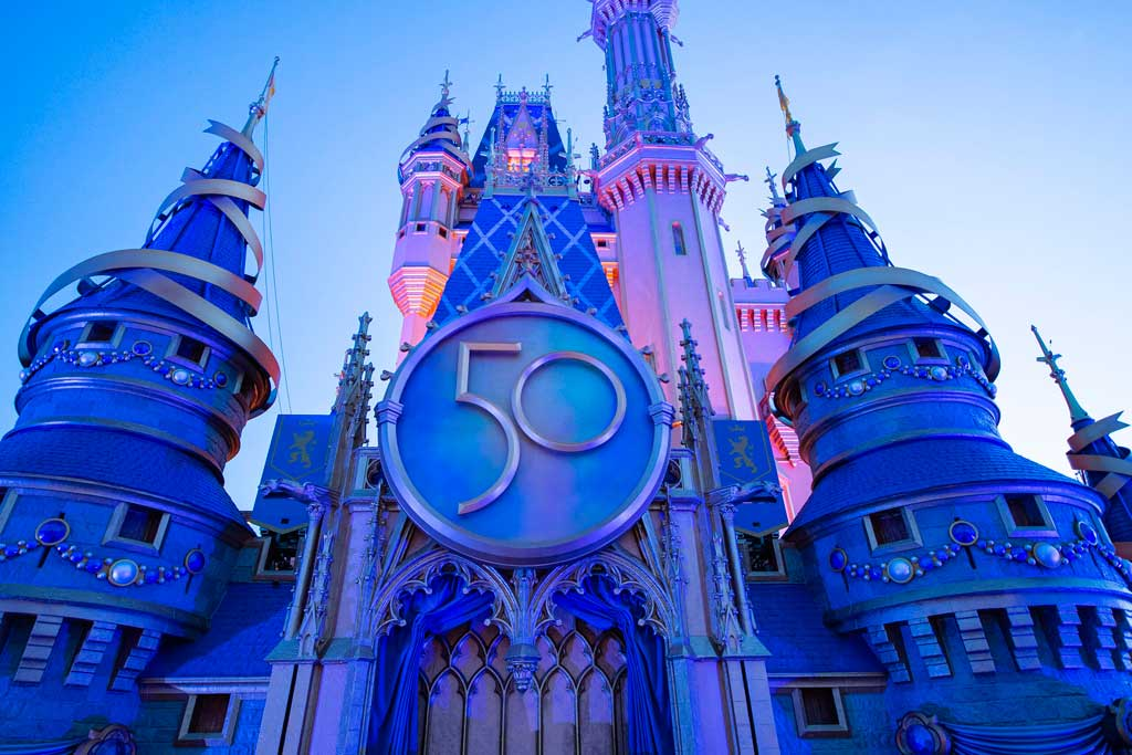 """A new crest honoring the 50th anniversary of Walt Disney World Resort adorns Cinderella Castle at Magic Kingdom Park in Lake Buena Vista, Fla. The crest completes the castle's royal, EARidescent makeover, joining gold bunting, sparkling embellishments and other new enhancements leading up to """"The World's Most Magical Celebration"""" beginning Oct. 1, 2021. (Kent Phillips, photographer)"""