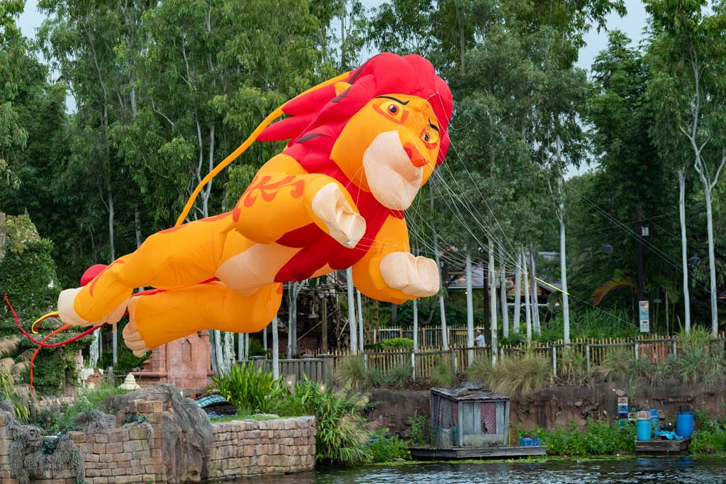 """New daytime entertainment is stirring at Disney's Animal Kingdom Theme Park, as """"Disney KiteTails"""" comes alive several times daily beginning Oct. 1, 2021, at Walt Disney World Resort in Lake Buena Vista, Fla. Performers fly windcatchers and kites of all shapes and sizes, while out on the water elaborate three-dimensional kites – some stretching to 30 feet long – depict Disney animal friends, including Simba, Zazu, Baloo and King Louie. These colorful creations dance through the sky to the beat of favorite Disney songs in an uplifting, vibrant experience for the whole family. (Matt Stroshane, photographer)"""